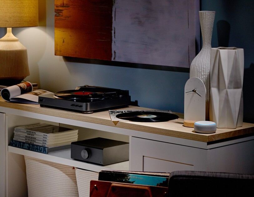 An Echo Link Amp in a living room setting. Surround it are magazines, records, a record player, lamp, decorations and Echo Dot device.