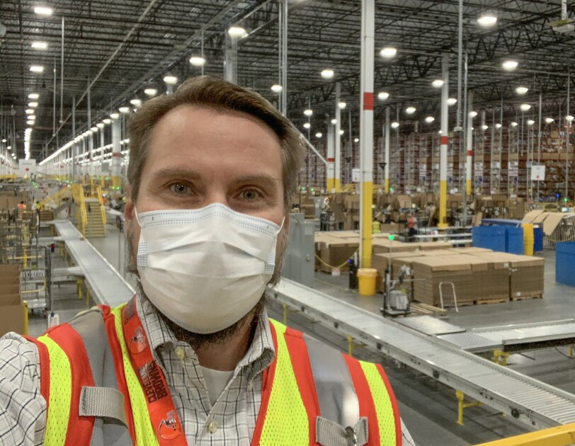 A man wearing a protective mask and a safety vest stands in front of a large warehouse space.