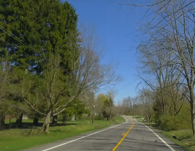 Ohio countryside with a two-lane road running through trees and rolling lawns.
