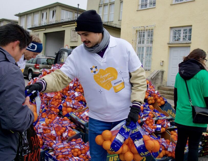 """Ein Volunteer von Amazon, gekleidet im weißen Shirt mit Aufdruck """"Amazon Volunteers"""", gibt Orangen an Bedürftige aus."""