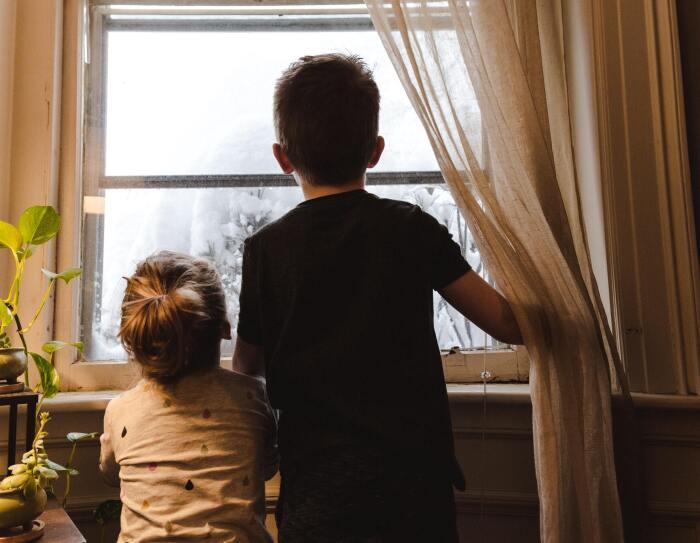 Doa heramos: una hermana de unos 3 años y un hermano de unos 7 años. Los dos están de espaldas y mirando por una ventana. El niño va con una camiseta negra de manga corta. La niña, con una camiseta blanca y con lágrimas de colores. Fuera de la ventana se ve todo blanco y parece que hay un árbol con nieve. El niño con la mano derecha aguanta unas cortinas blancas. El marco d e la ventana es blanco y de madera. En laparte izquierda de la foto hay un mueble con 4 plantes y se nota que entra la luz de una lámpara.