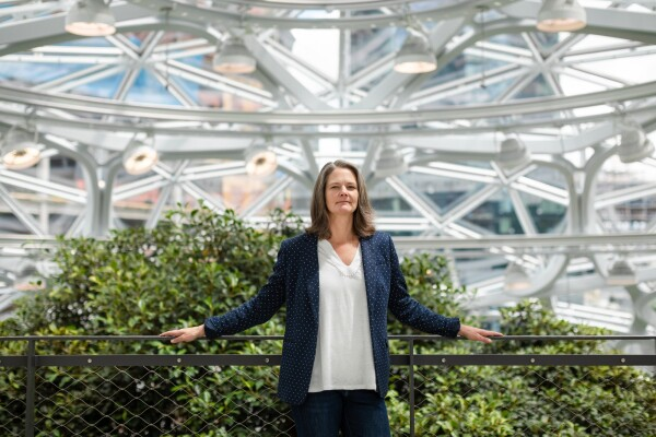 A woman in a blue and white suit, and a white blouse, is photographed inside The Seattle Spheres, a geometric greenhouse with plants from the Pacific Northwest. The background is the geometric windows of The Spheres, with the Seattle skyline in the background.