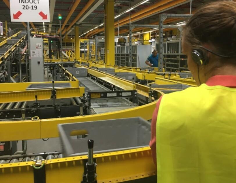 Eine Besucherin betrachtet die Förderbänder im Logistikzentrum Frankenthal