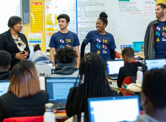 A teachers stands in front of her class alongside three Amazon Future Engineer volunteers.