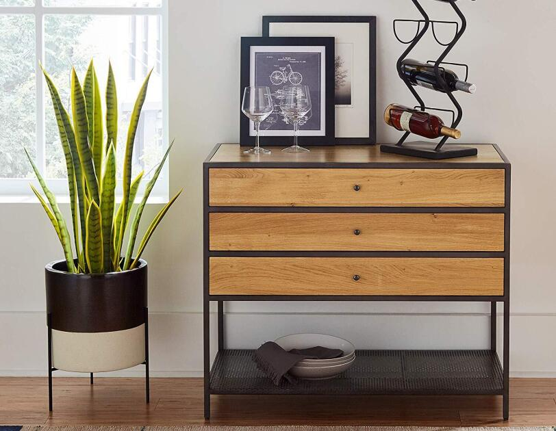 A raised pot on three feet holds a tall green plant. To the right of the plant is a three drawer sideboard with a wine rack, two wine glasses and framed art on top of it. In front the sideboard and plant is a woven rug.