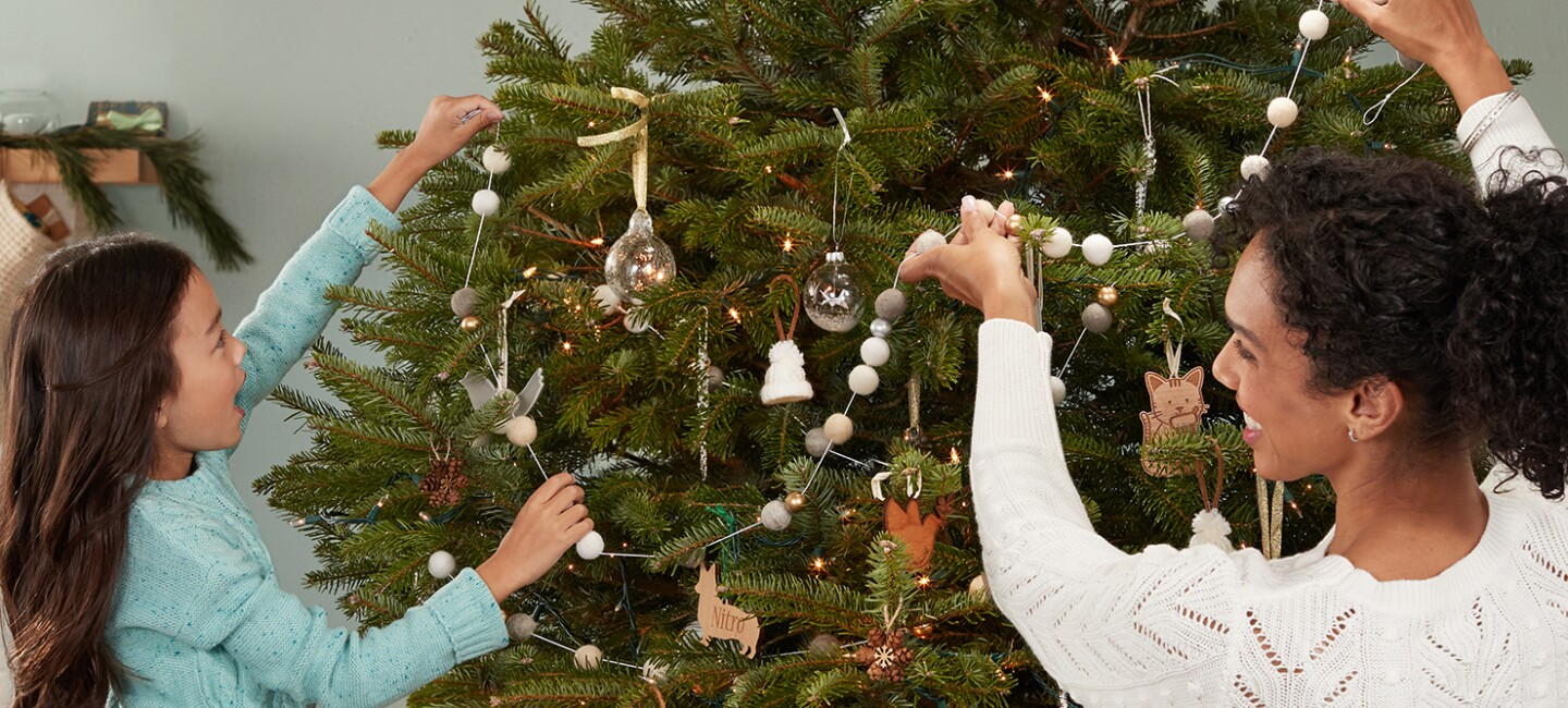A woman and child decorate a Christmas tree in  a home. They're hanging a string of felted balls among ornaments and lights.