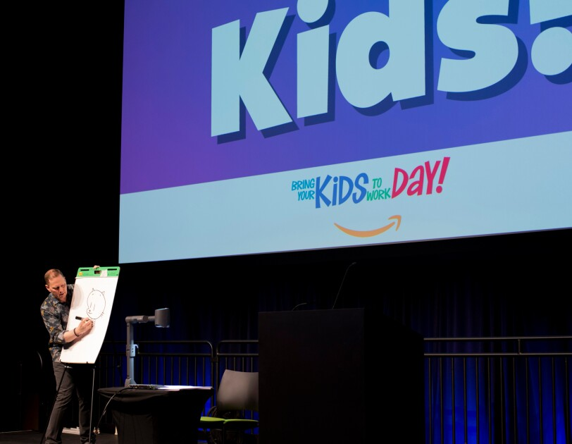 """A man draws a cartoon cat figure on an easel. He is flanked by a large screen with the words """"Bring Your Kids to Work Day!"""" and the Amazon smile logo."""