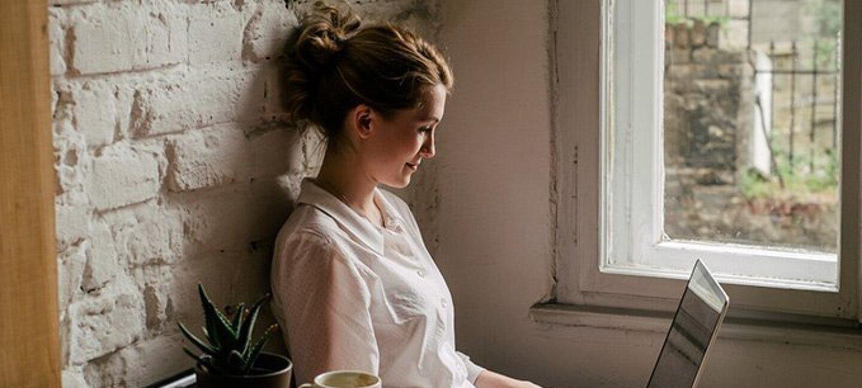 Une jeune femme est assise devant une table avec un café et une plante, elle est en train de travailler avec son ordinateur sur ses genoux