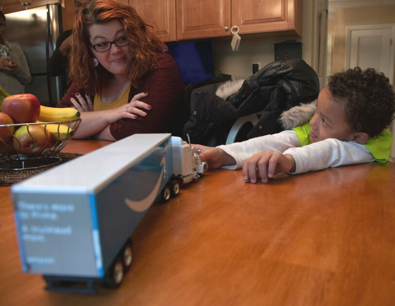 A woman and a boy sit together at a table. On top of the table is a toy semi truck with the Amazon smile logo.