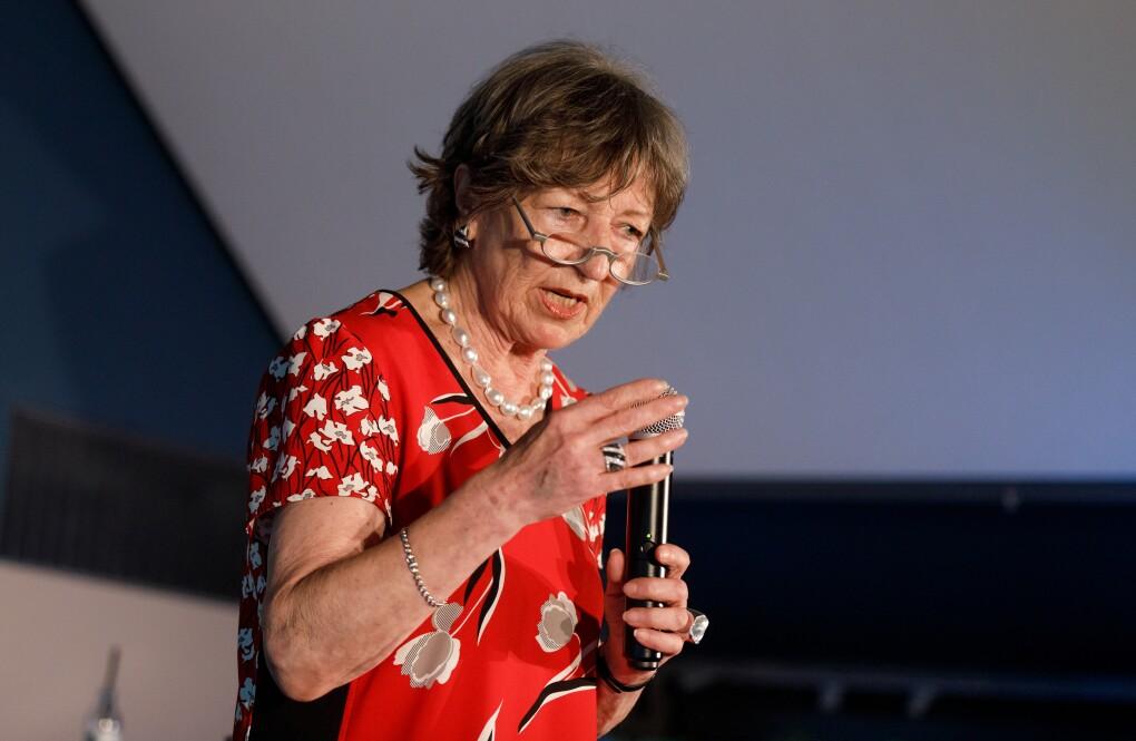 Eva-Maria Roer steht auf Bühne, sie hält ein Mikrofon in der Hand und blickt ins Publikum