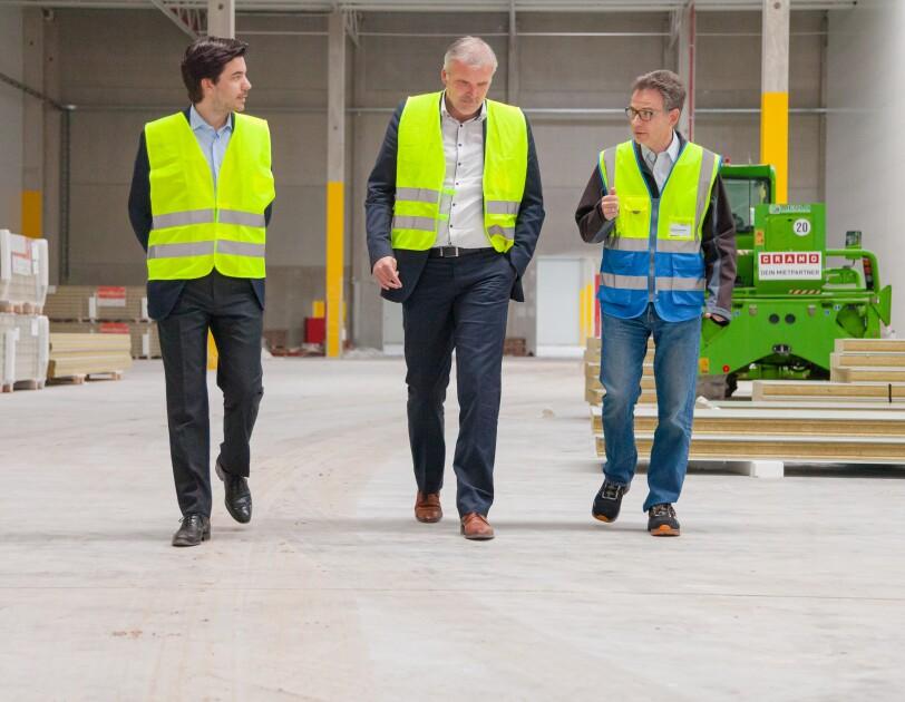3 Männer in gelben Sicherheitswesten gehen Seite an Seite durch eine Halle.