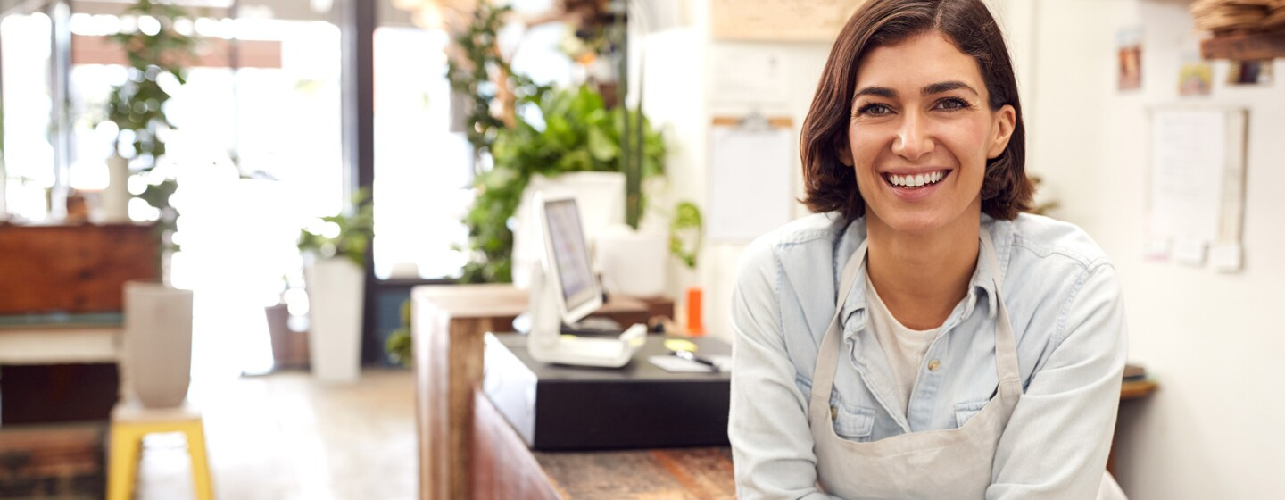A woman working in a small business leans toward the camera.