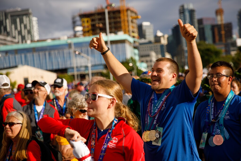 Special Olympics athletes and closing ceremony attendees celebrate. Many people looking toward the stage, with a male athlete giving thumbs up while smiling.