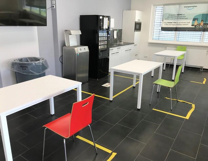 Ein Raum mit Küchenzeile, weißen Tischen und bunten Stühlen.