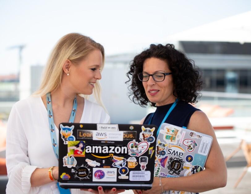 Zwei Frauen halten einen Laptop in den Händen auf dem Amazon steht. Sie sprechen miteinander.