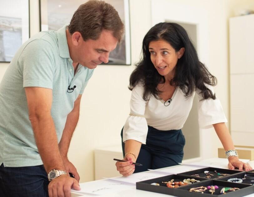 Maria A. Marinas von Gemshine bespricht sich mit einem Kollegen zu Schmückstücken, die auf dem Tisch liegen.