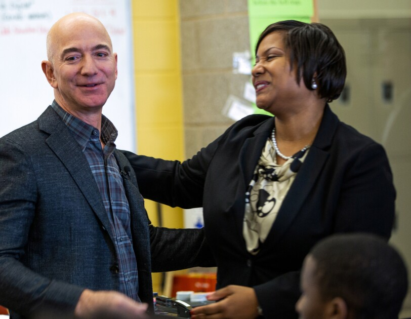 A teacher in a classroom greets Jeff Bezos.
