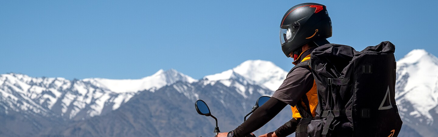 A helmeted motorcyclist wears a large black backpack with the Amazon smile logo. Snow-capped mountain peaks are in the background of the image.
