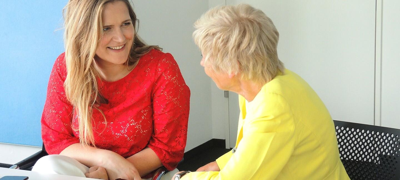 Eine Frau erklärt eine älteren Dame, wie ein Smartphone funktioniert
