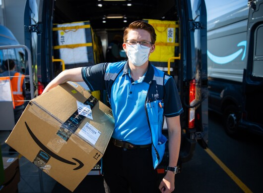 An Amazon delivery driver stands for a photo in front of his delivery van, holding a box and smiling under a mask.
