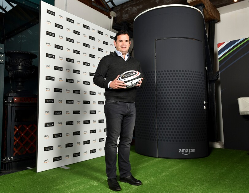 Will Carling standing holding a rugby ball at the Six Nations promoting AWS. He is standing in front of a large Amazon Alexa Echo model.