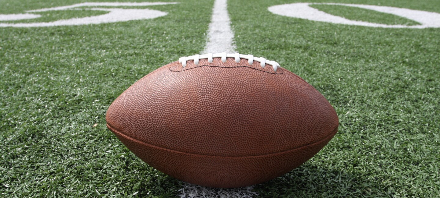 An inflated football sits on a yard line of an American football field.