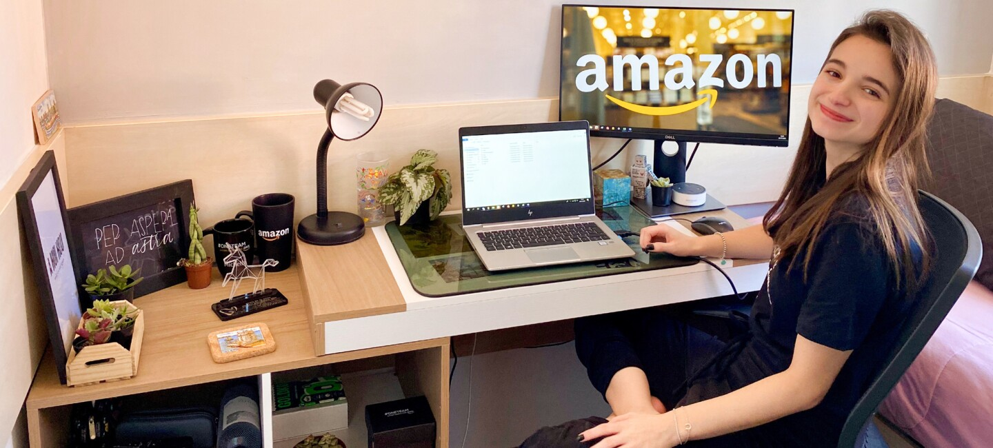A woman sits at a desk with a laptop and a monitor showing the Amazon logo.
