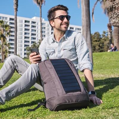 Der Gründer von SunnyBag sitzt in der Sonne, auf einer Wiese.