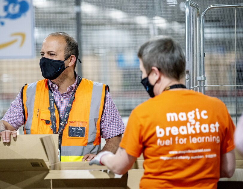 Two Amazon employees pack food parcels for Magic Breakfast