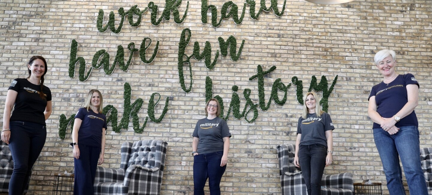 """Amazon employees, and ex-veterans from the Warriors@ affinity group staniding in front of a sign which reads """"work hard, have fun, make history""""."""