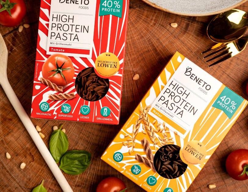 Auf einem Braunen Tisch liegen zwei Nudelverpackungen der Marke Beneto Foods. Daneben liegen Tomaten, Basilikum und ein Kochlöffel.