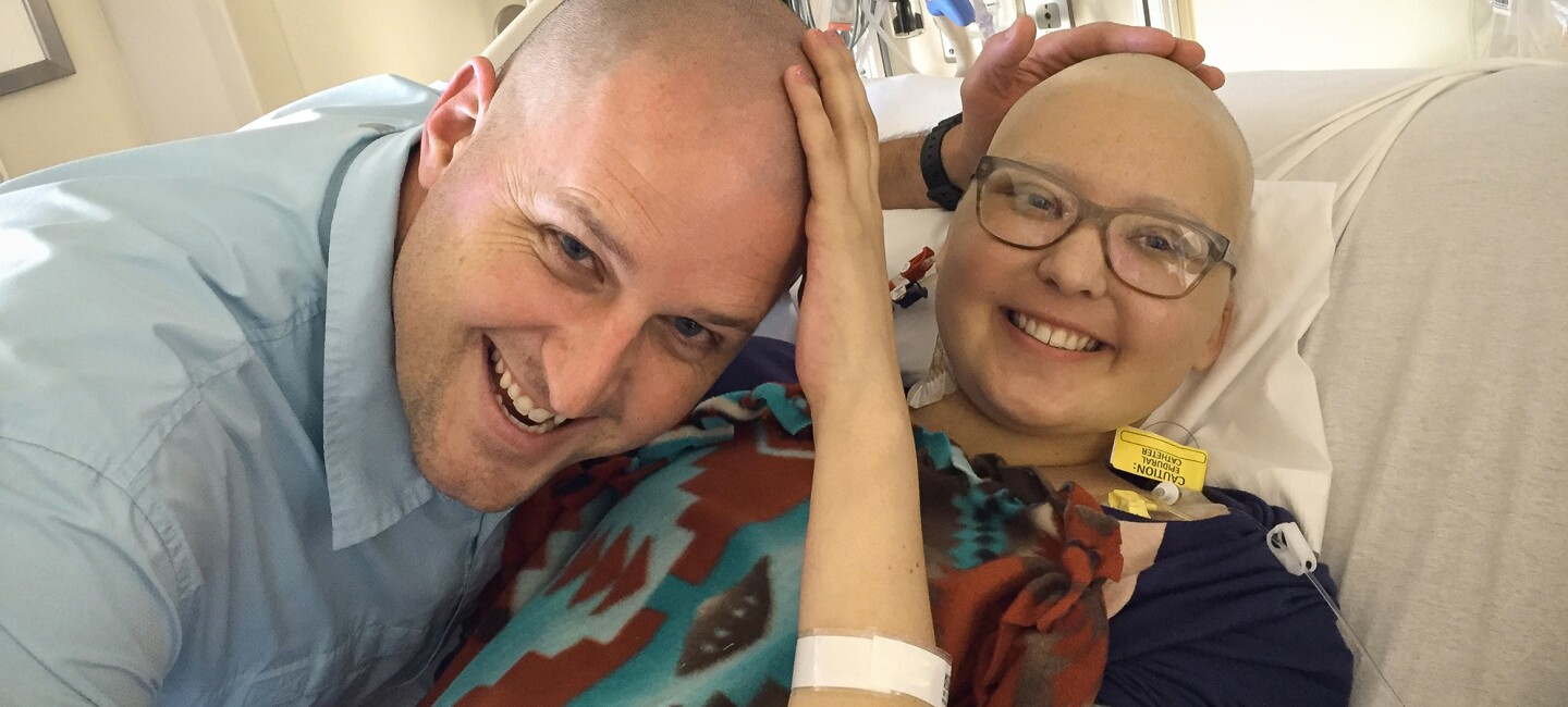 A father leans in to hug his daughter in a hospital bed. Both of them are bald.