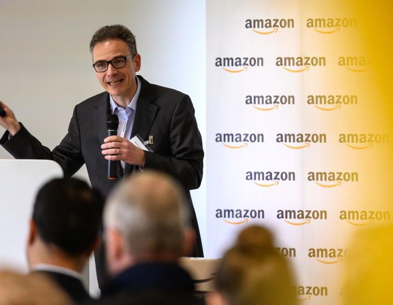 """Ein Mann mit Mikrofon in der Hand, im Hintergrund sieht man eine Logo-Wand mit Aufschrift """"Amazon"""""""