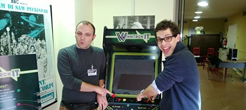 Due ragazzi di fronte a un videogioco in un ufficio.