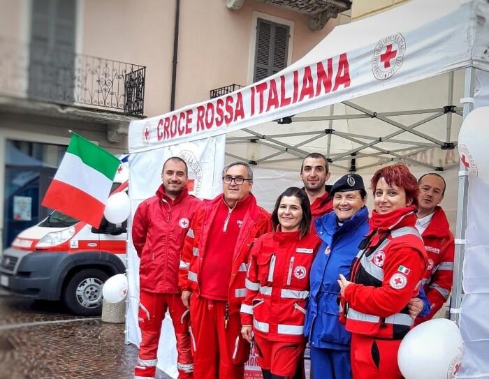 Volontari della Croce Rossa in gruppo sotto uno stand all'aperto.