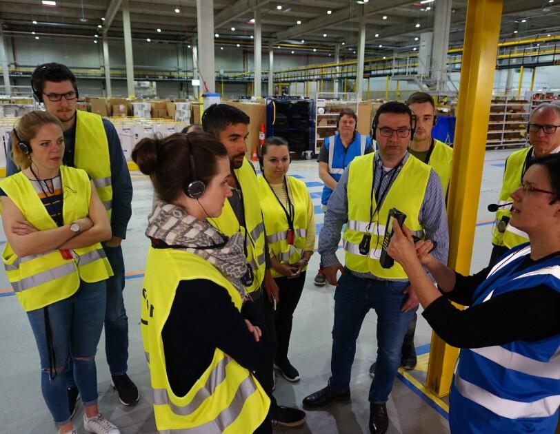 Einer Besuchergruppe steht für einer Amazon Mitarbeiter, die einen Scanner in der Hand hält