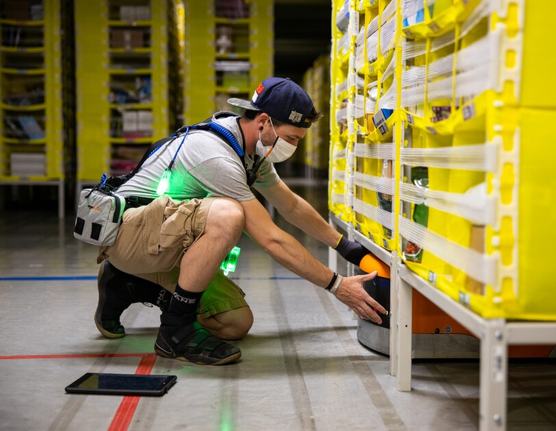 A man at an Amazon fulfillment center neals in front of a yellow storage tower, reaching under to maneuver an orange robot.