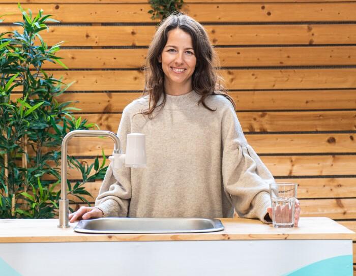 La start-up TAPP Water fue fundada por Magnus Jern y Alexander Schwarz. En la foto aparece la CEO Rocío Alcocer en una mesa con un gripo que tiene el filtro de Tapp water . Rocío va un jersey también marrón muy claro. Tiene el pelo largo castaño y las manos apoyadas sobre la mesa, sujerta una vaso de cristal con agua. De fondo una pared de madera.