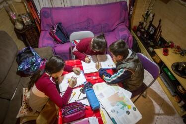Tres niños, dos niñas y un niños, trabajando en una mesa situada en el salón de una casa. Dos de ellos están sentados enuna silla y la tercera está sentada en el sofà. Dos de ellos trabajan sobre el mismo libro. Hay dos sofás y en la mesa hay libros, lápices y rotuladores. Los tres van muy abrigados y tienen las mochilas tiradas por el sofá.