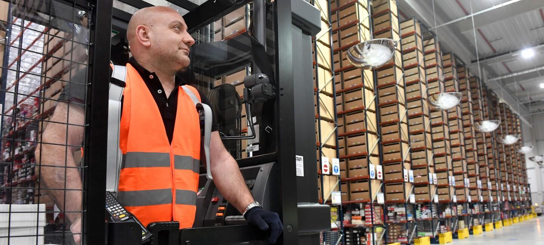 Ein Hochregalstapelfahrer blickt auf die mit Hochregalen bestückte Logistikhalle