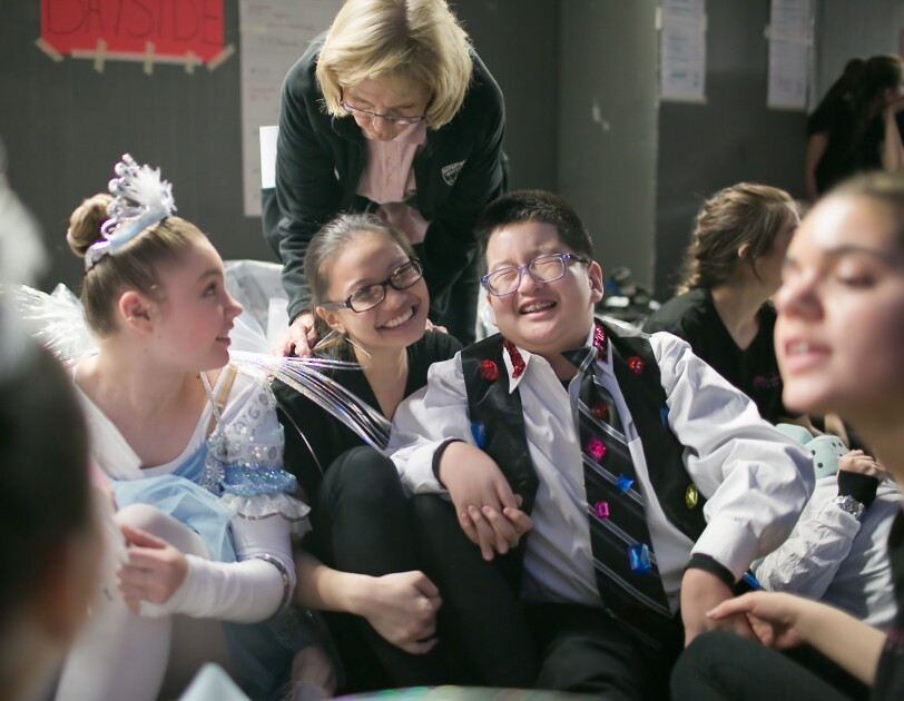 A boy and several girls sit together backstage. They are wearing dance costumes. In the background, a woman leans down.