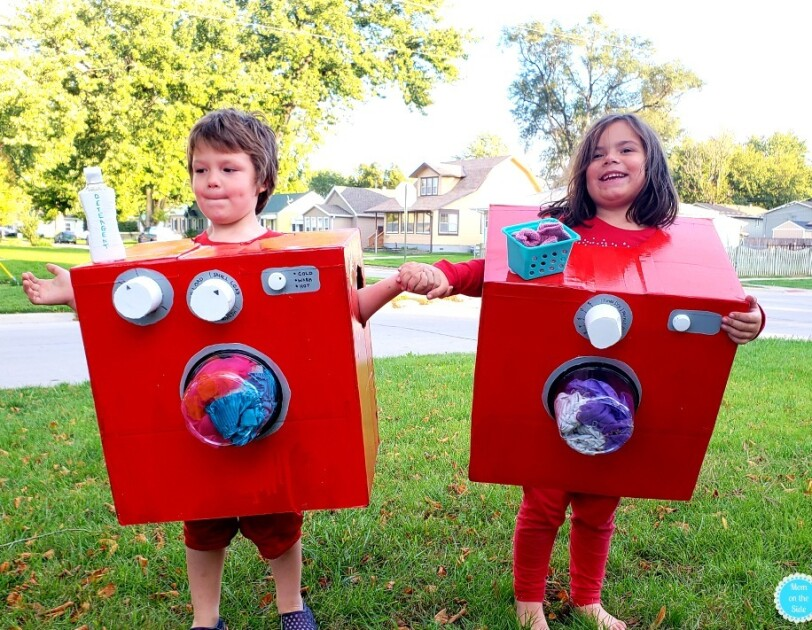 """Two young children stand side-by-side, each wearing a red box. Both boxes have a clear """"window"""" on the front that shows clothing, which look as though they're tumbling in the laundry. The child on the left has a bottle that says """"detergent"""" on the top of the box, and two knobs. The child on the right has a small basket that looks like a laundry basket with socks, and one knob."""