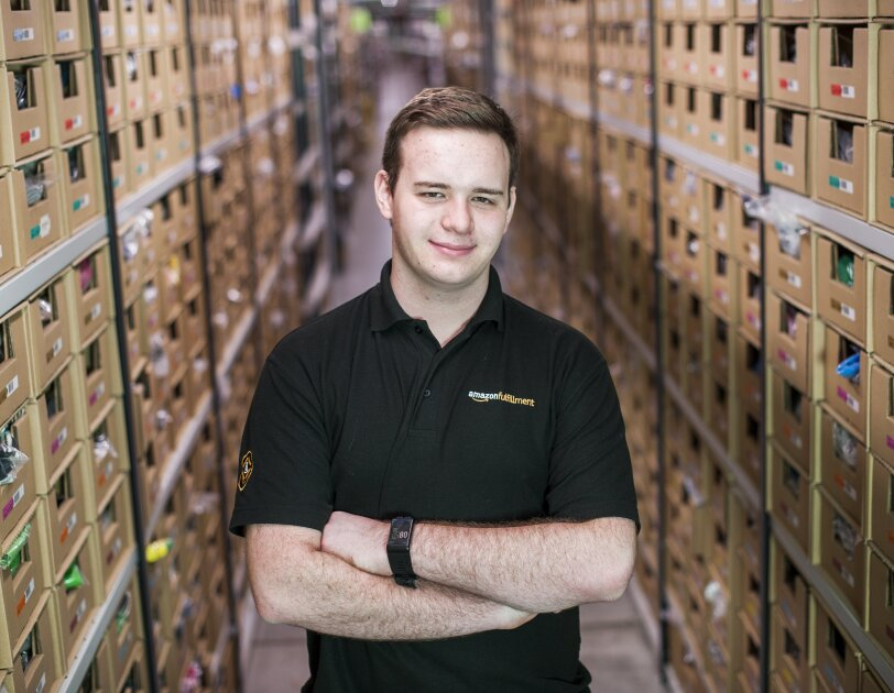 Jonathon Williams stood in Amazon Fulfilment Centre with arms crossed