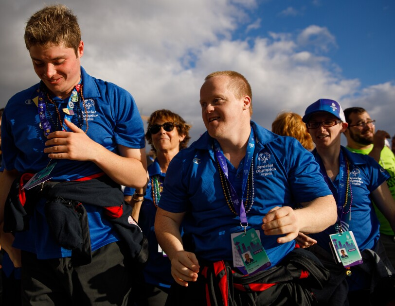 """Special Olympics athletes and attendees from Virginia appear to lead a group of others. Two smiling males are in the foreground, seeming to be moving forward. In the middle ground, two other individuals wearing """"Special Olympics Virginia"""" shirts are facing the same direction. In the background, more attendees are seen."""