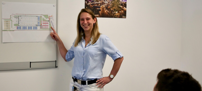 Mitarbeiterin mit halblangen blonden Haaren, blauer Bluse, weißen Jeans, vor dem Flipchart