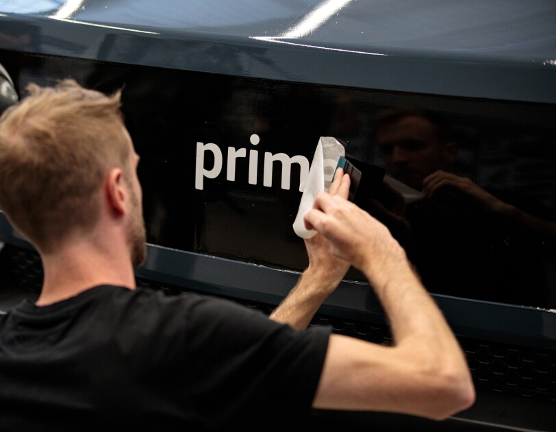 A man peels the backing off stickers to reveal the first four letters of a Prime logo.
