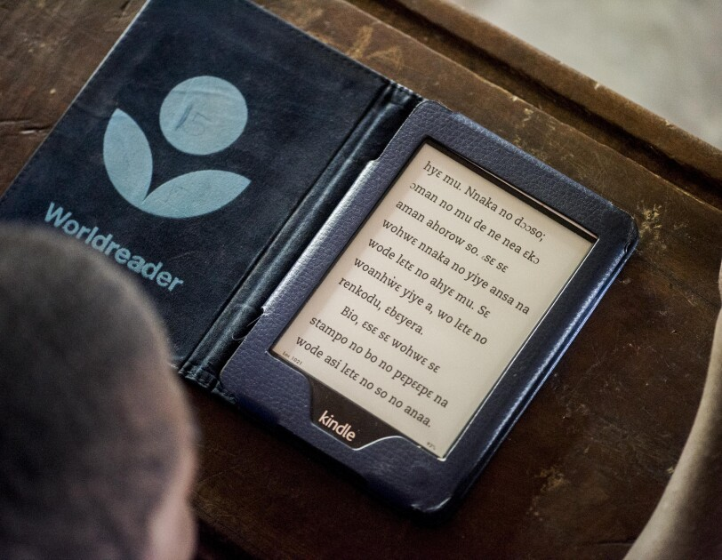 The black and white screen of a Kindle on a wooden desk. The Worldreader logo is on the left flyleaf.