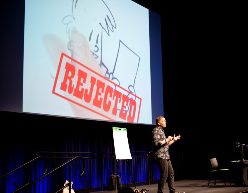 "A man stands on a stage in front of a big screen that shows a cartoon figure and the word ""REJECTED."""