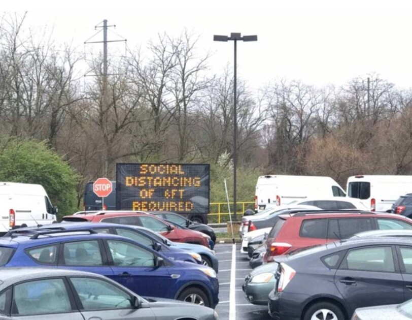 "View from an Amazon fulfillment center parking lot showing cars that have parked. In the background is a sign that says ""Social distancing of 6 ft required."""