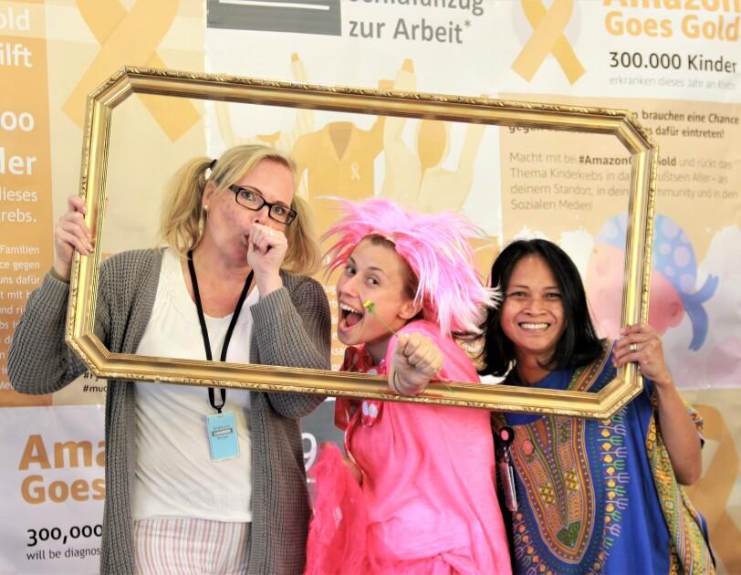 3 Mitarbeiterinnen im Schlafdress hinter einem Fotorahmen, vor einer Fotoleinwand mit Goes Gold